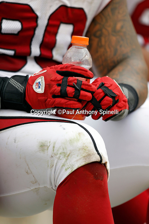 An Arizona Cardinals player takes a drink break while wearing team colored gloves during the NFL week 17 football game against the San Francisco 49ers on Sunday, January 2, 2011 in San Francisco, California. The 49ers won the game 38-7. (©Paul Anthony Spinelli)