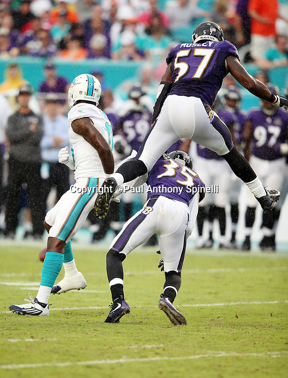 Baltimore Ravens inside linebacker C.J. Mosley (57) leaps over Baltimore Ravens defensive back Shareece Wright (35) as the two defenders break up a pass play intended for Miami Dolphins wide receiver DeVante Parker (11) during the 2015 week 13 regular season NFL football game against the Miami Dolphins on Sunday, Dec. 6, 2015 in Miami Gardens, Fla. The Dolphins won the game 15-13. (©Paul Anthony Spinelli)