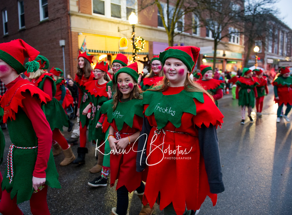 """Glitter"" and ""Freckles"" march with their fellow elves from Santa's Village during Light Up Laconia's Holiday Parade on Sunday.  (Karen Bobotas/for the Laconia Daily Sun)"