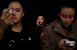 Models look at their mobile phones as they wait backstage before the Minzu University of China Collection  show during the Mercedes-Benz China Fashion Week in Beijing, China, 27 March 2013. The Mercedes-Benz China Fashion Week will run from 25 to 30 March.