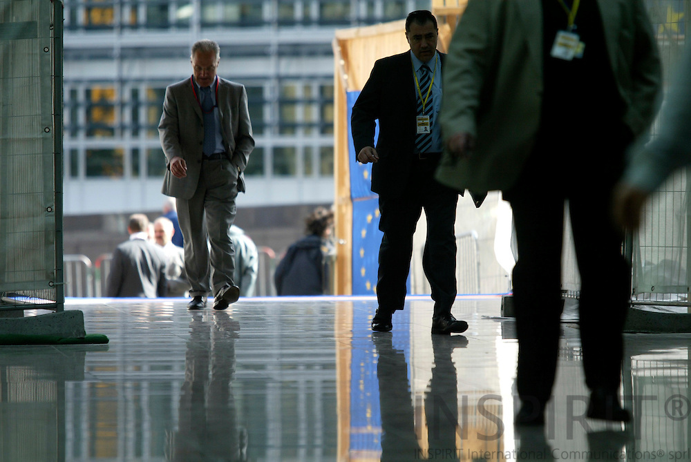 BRUSSELS - BELGIUM - 16 JUNE 2006 -- European Civil Servants mirrored in the tiles on the floor walking at the entrance to the EU Council with EU Flags in background and the Berlaymont.  PHOTO: ERIK LUNTANG /