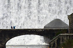 © Licensed to London News Pictures. 06/01/2018. Elan Valley Reservoirs, Powys, Wales, UK.  People cross a bridgeas water rages over the Caban Coch dam near Rhayader, Powys, Wales. The Elan Valley reservoir complex has been replenished after heavy rainfall from Storm Eleanor and melting snow which fell in December 2017. Birmingham's Frankley reservoir is supplied by Elan Valley reservoirs on a gravity feed over a distance of 73 miles (117 Km.) Photo credit: Graham M. Lawrence/LNP
