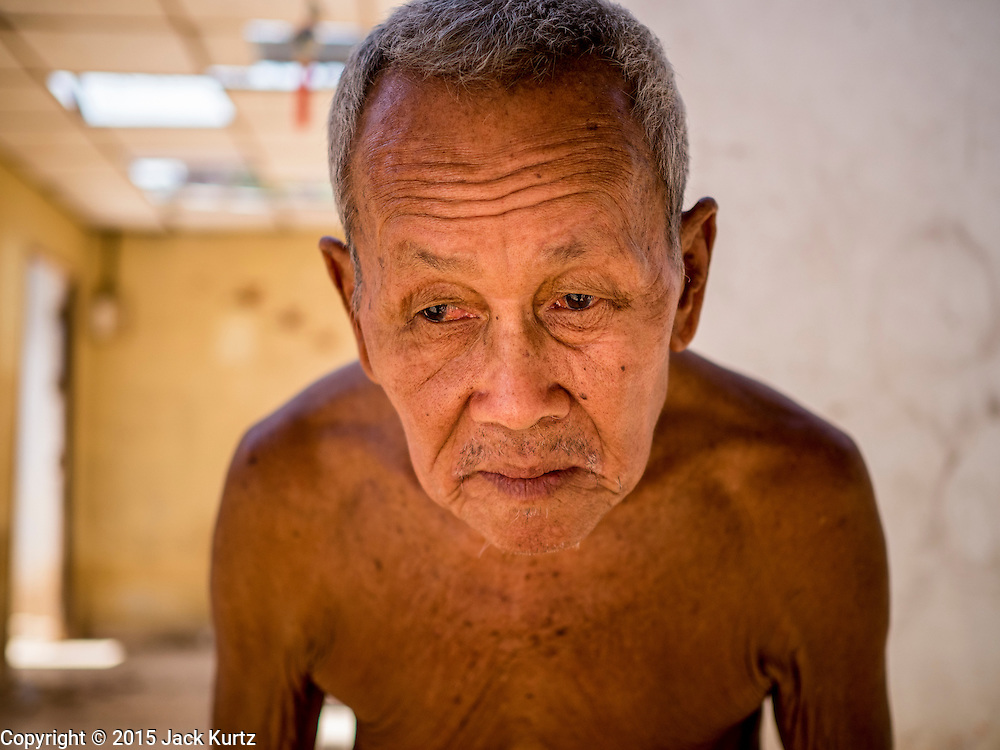 01 JULY 2015 - THA CHAI, CHAI NAT, THAILAND:  SAMPHONG, 81 years old, who lives along the Chao Phraya River in Chai Nat province walks away from his home, most of which slid into the river after the land under the home collapsed because of drought. He is hoping to rebuild on the same land, but the government said it could be a year before he can move back in. Central Thailand is contending with drought. By one estimate, about 80 percent of Thailand's agricultural land is in drought like conditions and farmers have been told to stop planting new acreage of rice, the area's principal cash crop. Water in reservoirs are below 10 percent of their capacity, a record low. Water in some reservoirs is so low, water no longer flows through the slipways and instead has to be pumped out of the reservoir into irrigation canals. Farmers who have planted their rice crops are pumping water out of the irrigation canals in effort to save their crops. Homes have collapsed in some communities on the Chao Phraya River, the main water source for central Thailand, because water levels are so low the now exposed embankment is collapsing. This is normally the start of the rainy season, but so far there hasn't been any significant rain.    PHOTO BY JACK KURTZ