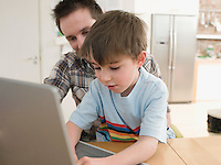 Father Helping Son Use Laptop