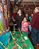 Union Sanborn 1st grader Teagan Nelson along with her sister Loralie, mom Toni and Scott Gloddy search for Teagan's artwork on the wall at the Arts Alive event at the Belknap Mill Thursday evening.    (Karen Bobotas/for the Laconia Daily Sun)