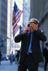 Bisinessman upset while talking on a cellphone downtown Wall Street area