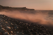 Motion of a wave as it hits the boulders high up on Kilve beach as sunset approaches, with the Quantock cliffs at East Quantoxhead in the background.