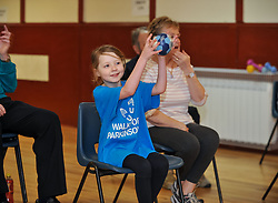 Pictured: Abby McConnell takes part in one of the excercises which involves catching a ball and throwing it back.<br /> <br /> A young fundraiser inspired by comedian Billy Connolly's battle with Parkinson's  prepares for a charity walk on April 15th - World Parkinson's Day - to raise funds for the charity. Abby McConnell (7) from Mount Florida met sufferers and took part in a seated exercise class specially designed for sufferers of the disease at Rutherglen West Parish Church in Glasgow.<br /> <br /> &copy; Dave Johnston / EEm