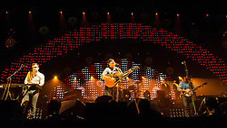 "© Licensed to London News Pictures. 11/12/2012. London, UK.  Ben Lovett (left), Marcus Mumford (centre) and Winston Marshall (right) of  Mumford & Sons performing live at The O2 Arena. Mumford & Sons are an English folk rock band. The band consists of Marcus Mumford (vocals, guitar, drums, mandolin), Ben Lovett (vocals, keyboards, accordion, drums), ""Country"" Winston Marshall (vocals, banjo, dobro, guitar), and Ted Dwane (vocals, string bass, drums, guitar).  Photo credit : Richard Isaac/LNP"