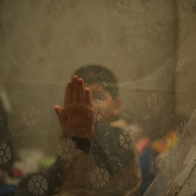 DONETSK, UKRAINE - OCTOBER 18, 2014: A child is seen sitting in a bed surrounded by a mosquito net at a bomb shelter in Donetsk's Petrovskiy District. Some of the around hundred residents moved to the old shelter almost four months ago, as when of the beginning of a major offensive against the city by the Ukrainian National Guard. Many of the city's residential areas have been increasingly destructed by regular shelling from both the Ukrainian troops and rebel forces. CREDIT: Paulo Nunes dos Santos