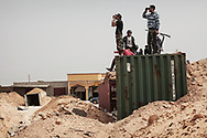 Observing a long and  empty stretch of road toward Zliten, Libyan rebels on the watch at a road block made of shipping containers and sand berms on Ald Dafniyah front line, 25 km west of Misrata. 22 May 2011.