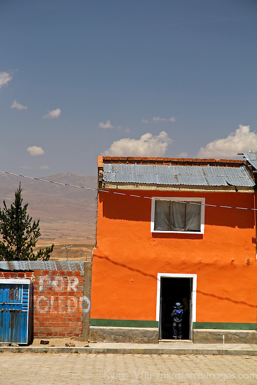 South America, Bolivia, Calamarca. Boy stands in the door of a Calamarca home.