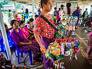 20 NOVEMBER 2017 - YANGON, MYANMAR: A toy vendor on the Dala Ferry. There are vendors selling fruit, snacks, betel, toys, and phone SIM cards on the ferry. People getting off the Dala Ferry in Yangon leave the ferry terminal. Tens of thousands of commuters ride the ferry every day. It brings workers into Yangon from Dala, a working class community across the river from Yangon. A bridge is being built across the river, downstream from the ferry to make it easier for commuters to get into the city.     PHOTO BY JACK KURTZ