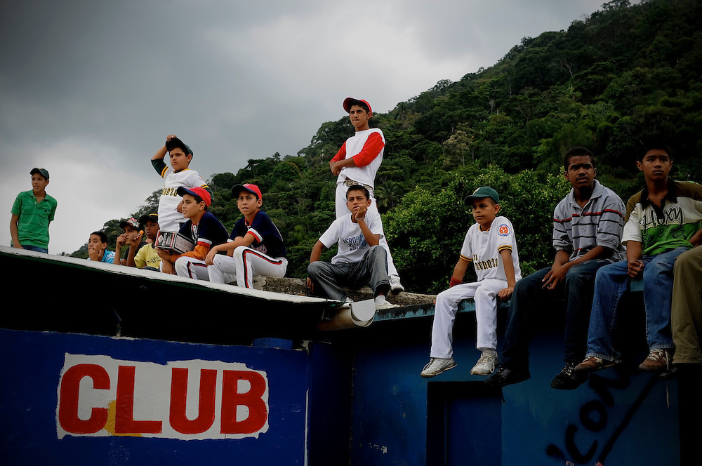 Kids watch the 2009 championship little league game from the roof of the dugout where Mets' pitcher Johan Santana grew up playing baseball. Santana went back to Tovar, Venezuela last weekend for an annual charity event thrown by the Johan Santana Foundation and passed out 10,000 toys to local children. Before throwing the opening pitch of the little league championship, Santana also surprised every team in the league with new equipment.