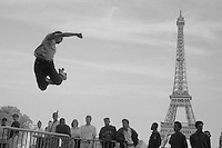 Roller skaters performing jumps with the Eiffel Tower in the background. Plateau Joffre, Paris France June 1991