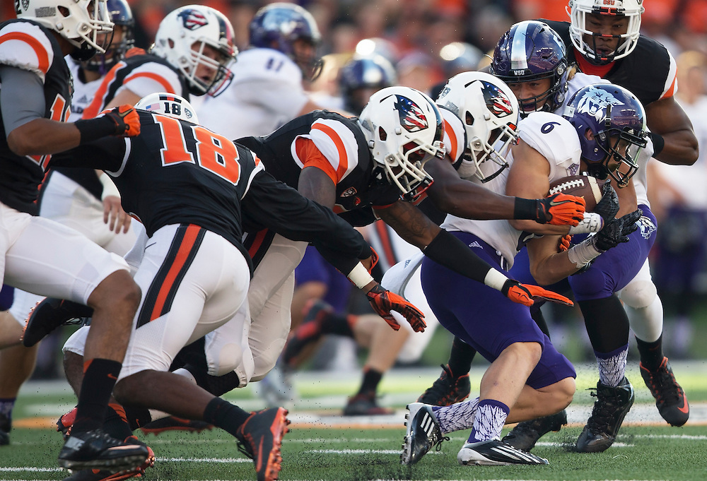 Weber State's Drew Batchelor (right) drags members of the Oregon State defense while carrying the ball Oregon State's 26-7 victory in the 2015 season opener in Reser Stadium, in Corvallis, on Friday, Sept. 4, 2015.