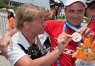 (R) athlete Jacek Cieslik of SO Poland with his trainer after cycling competition during 2011 Special Olympics World Summer Games Athens on June 27, 2011..The idea of Special Olympics is that, with appropriate motivation and guidance, each person with intellectual disabilities can train, enjoy and benefit from participation in individual and team competitions...Greece, Athens, June 27, 2011...Picture also available in RAW (NEF) or TIFF format on special request...For editorial use only. Any commercial or promotional use requires permission...Mandatory credit: Photo by © Adam Nurkiewicz / Mediasport