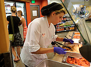 Patience Melton, 21, works at the Whole Grocer on Monday, bringing more chicken tenders to the hot-food bar.
