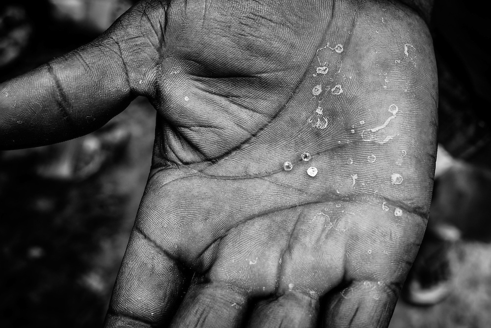 A man holds out 3 tiny diamonds in his palm. John Logan Town, Liberia.