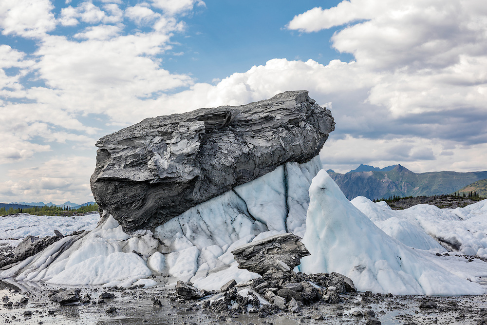 Compacted glacial silt sits on a pedestal of melting ice on Matanuska Glacier in Southcentral Alaska. Summer. Afternoon.