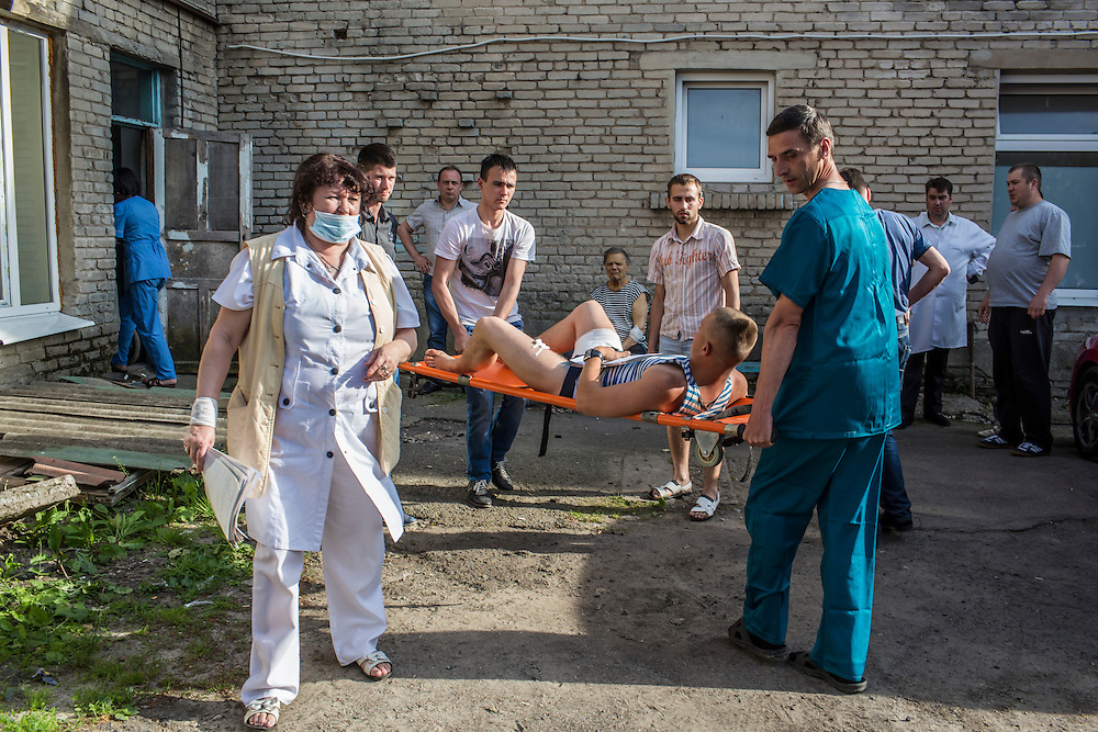VOLNOVAKHA, UKRAINE - MAY 22:  A Ukrainian soldier wounded earlier in the day during an attack on a military checkpoint by unknown forces is transfered to a waiting ambulance on May 22, 2014 in Volnovakha, Ukraine. Authorities reported fifteen soldiers were killed and 31 injured. (Photo by Brendan Hoffman/Getty Images) *** Local Caption ***