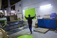 SOVERIA MANNELLI, ITALY - 16 NOVEMBER 2016: A worker carries a beechwood board that will be cut and become a desk at Camillo Sirianni, a school furniture manifacturer in Soveria Mannelli, Italy, on November 16th 2016.<br /> <br /> Camillo Sirianni is a third generation family business that started as a family mechanized carpentry in 1909 and transformed into a leading school furniture manufacturer. In a high-tech warehouse in the outskirts of Soveria Mannelli, they assemble thousands of Calabrian beechwooden, colorful desks, benches, closets and other accessories that are later shipped to many corners of the globe, from the United Kingdom to the Emirates, from central America to Polynesia.<br /> <br /> Soveria Mannelli is a mountain-top village in the southern region of Calabria that counts 3,070 inhabitants. The town was a strategic outpost until the 1970s, when the main artery road from Naples area to Italy's south-western tip, Reggio Calabria went through the town. But once the government started building a motorway miles away, it was cut out from the fastest communications and from the most ambitious plans to develop Italy's South. Instead of despairing, residents benefited of the geographical disadvantage to keep away the mafia infiltrations, and started creating solid businesses thanks to its administrative stability, its forward-thinking mayors and a vibrant entrepreneurship numbering a national, medium-sized publishing house, a leading school furniture manufacturer and an ancient woolen mill.