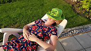 Woman in colourful dress and green hat napping on a plastic chair, Consecon, Canada.