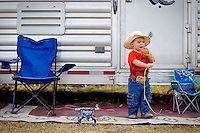 Radley Griggs, 2, plays with a rope while standing by his parent's livestock trailer Friday near the rodeo arena at the Kootenai County Fairgrounds.