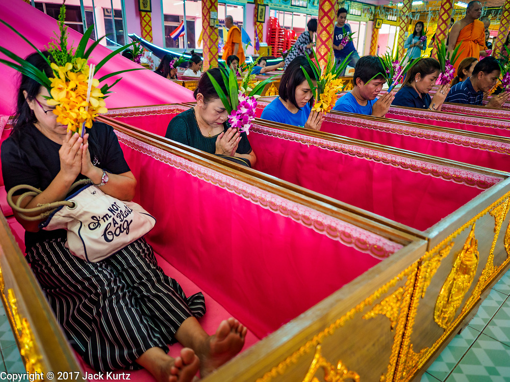 """24 JUNE 2017 - BANG KRUAI, NONTHABURI: People sit up in their coffins after being reincarnated during a """"resurrection"""" or rebirthing ceremony at Wat Ta Kien (also spelled Wat Tahkian), a Buddhist temple in the suburbs of Bangkok. People go to the temple to participate in a """"Resurrection Ceremony."""" Thai Buddhists believe that connecting people by strings around their heads, which are connected to a web of strings suspended from the ceiling, amplifies the power of the prayer. Groups of people meet and pray with the temple's Buddhist monks. Then they lie in coffins, the monks pull a pink sheet over them, symbolizing their ritualistic death. The sheet is then pulled back, and people sit up in the coffin, symbolizing their ritualist rebirth. The ceremony is supposed to expunge bad karma and bad luck from a person's life and also get people used to the idea of the inevitability of death. Most times, one person lays in one coffin, but there is family sized coffin that can accommodate up to six people. The temple has been doing the resurrection ceremonies for about nine years.     PHOTO BY JACK KURTZ"""