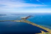 Nederland, Zeeland, Grevelingen, 01-04-2016; Grevelingendam gezien naar Bruinisse op Schouwen-Duiveland (aan de horizon). Naar links de Philipsdam naar Krammersluizen en St. Philipsland.  Rechts de Grevelingen of Grevelingenmeer, het grootste zoutwatermeer van Europa, ontstaan door het afsluiten van de zeearm door de Brouwersdam in het kader van de Deltatwerken (1971). <br /> The Grevelingendam, part of the Delta Works.<br /> luchtfoto (toeslag op standard tarieven);<br /> aerial photo (additional fee required);<br /> copyright foto/photo Siebe Swart