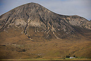 Lone remote crofter's farmhouse sits isolated beneath the 2,542 foot Glamaig mountain in dramatic landscape at Moll, Skye