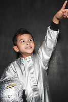 Portrait of young boy (5-6) in astronaut costume pointing upwards smiling studio shot