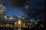 Hong Kong. Buildings Under Dark Clouds / Rain clouds gather over the Wan Chai district of , where a beam of sunlight reflects off of Central Plaza. the bay, Victoria island and harbour, towers   central plaza at sunset  / reflet sur líile victoria et la baie de  / P0001868  l940224d