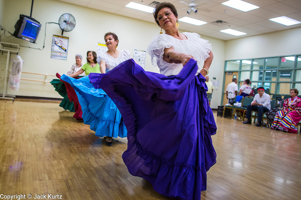 27 JUNE 2012 - GLENDALE, AZ:  MARGIE MAY, 65 years old, and other members of the Senior Fiesta Dancers perform during rehearsal for the Senior Fiesta Dancers at the Glendale Adult Center, in Glendale, AZ, a suburb of Phoenix. Dancing as a part of workout regimen is not unusual, but the Senior Fiesta Dancers use Mexican style folklorico dances for their workouts. The Senior Fiesta Dancers have been performing together for 15 years. They get together every week for rehearsals and perform at nursing homes and retirement centers in the Phoenix area once a month or so. Their energetic Mexican folklorico dances keep them limber and provide a cardio workout.   PHOTO BY JACK KURTZ