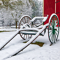 New England snow covered horse-drawn carriage in front of the red barn at the Longfellow's Wayside Inn. The Wayside Inn Historic District is located in Sudbury, Massachusetts. <br />