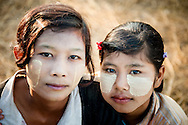 Myanmar, Ngapali. Portrait of two young girls from Ngapali who wear thanaka on their faces.<br />  Every single morning all the fisherman from the little village at Ngapali Beach come back home with their night catch. At the beach all the women wait for them and afterwards work with drying and selling fish and other creatures from the sea begins.
