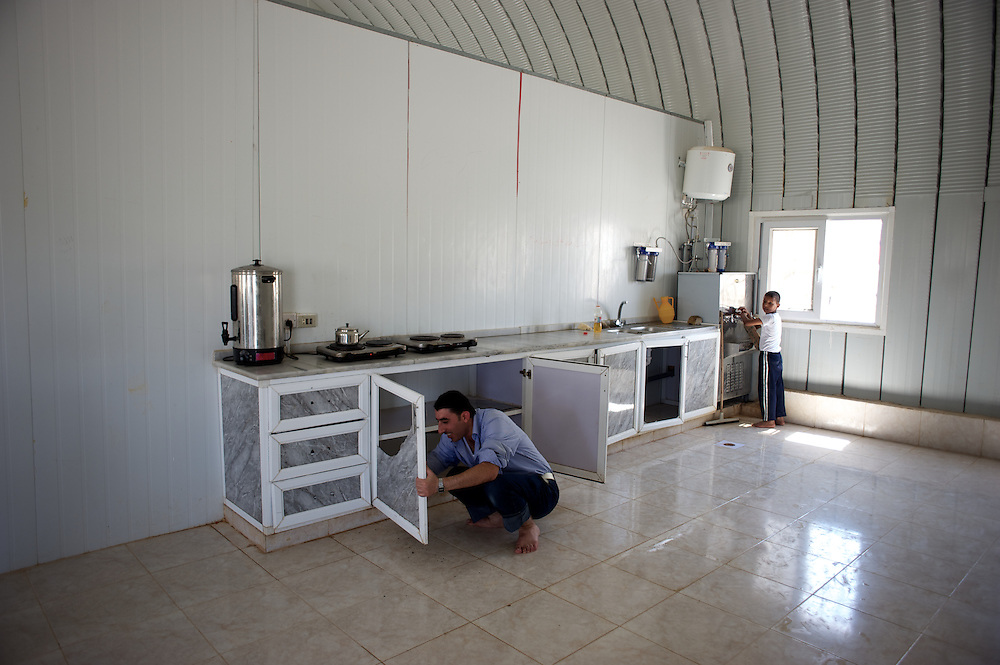 August 09, 2013 - Zarqa, Jordan: Syrian refugees clean the men's eating area at Mrigb Al-Fuhud refugee camp, also known as Emirates-Jordanian camp, 20 kilometres east of the Jordanian city of Zarqa.<br /> The 10 million USD camp, which has 750 caravans, a hospital, and a school and can take up to four thousand people, first opened in April 2013 and was paid for by the United Arab Emirates. Work is underway to house a total of 20 thousand by the end of the year. <br /> In contrast with the two other camps in the area, Mrigb Al-Fuhud as been classified by many as a 'five star' camp due to impressive housing facilities provided to the refugees. (Paulo Nunes dos Santos/Al Jazeera)