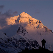 A climber is silhouetted against Mount Everest's North Face at sunset from Rongbuk Basecamp, Tibet.