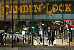 © Licensed to London News Pictures . FILE PICTURE DATED 09/08/2011. Camden , UK . Police standing beneath the iconinc Camden Lock rail bridge block roads leading in and out of Camden . Following a first night of riots and looting in Tottenham , rioting and looting spreads to other areas . Photo credit : Joel Goodman/LNP