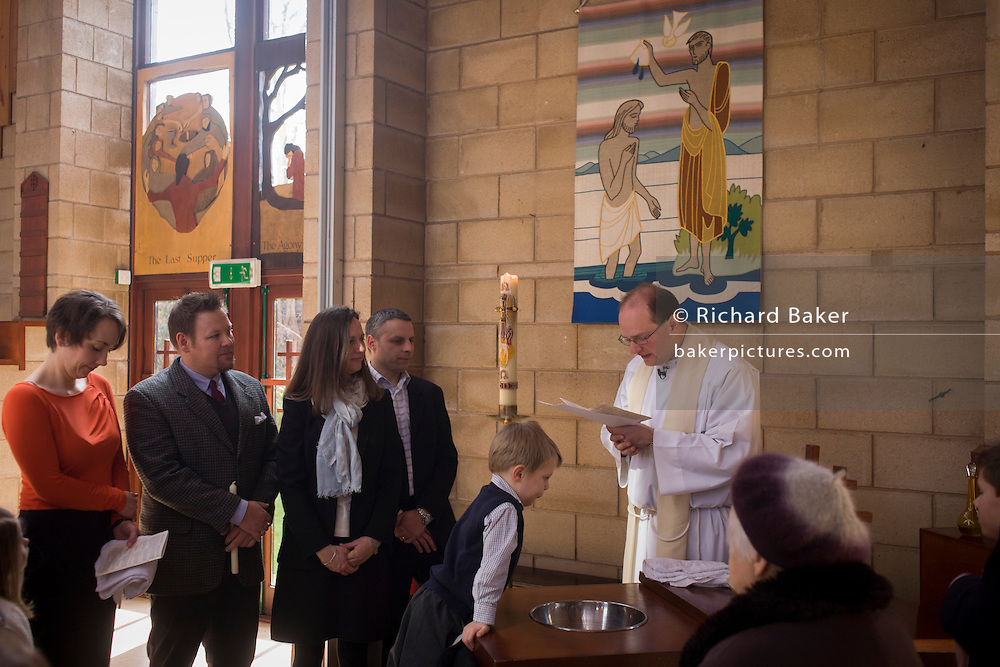 Family and relatives watch a 4 year-old's baptism ceremony in a local Catholic church