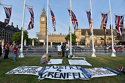© Licensed to London News Pictures. 19/06/2017. London, UK. Banners are laid out as people gather for a vigil in Parliament Square to remember those who died in the Grenfell Tower fire in North Kensington of 14 June.  Mourners and wellwishers were given the opportunity to speak and to write messages on a community banner.  Photo credit : Stephen Chung/LNP