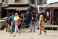 Young Nigerian woman in islamic headdress walking in street in Lagos, Nigeria.