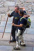 Pilgrims with walking poles end their pilgrimage in Cathedral square of Santiago de Compostela, Galicia, Spain