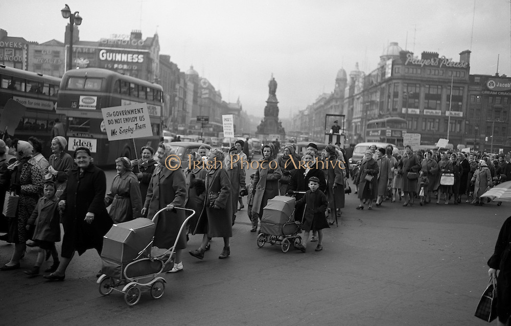 Housewives march in protest at the introduction of Turnover Tax, a new sales tax. The garda wearing white gloves in a raised booth to the centre right of the picture directed traffic on O'Connell Bridge. <br /> 14.11.1963