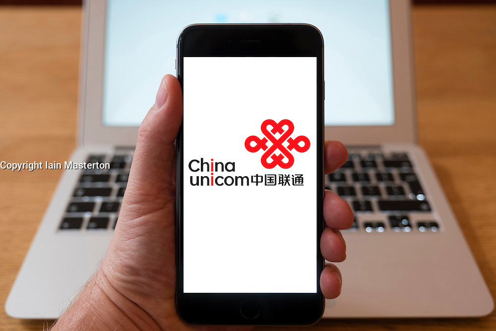 Using iPhone smartphone to display logo of China Unicom, Chinese state-owned telecommunications operator.