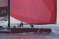 Italy's Capitalia foredeck crew stows genoa jib after hoisting spinnaker during America's Cup fleet race; Valencia, Spain.