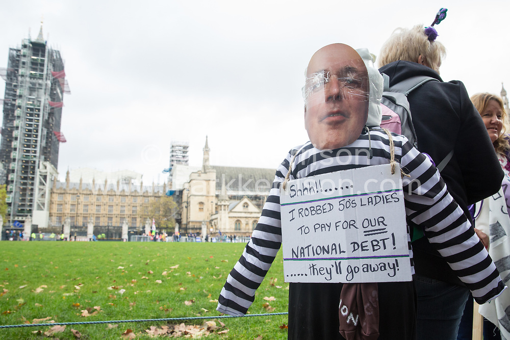 London, UK. 5 November, 2019. Campaigners from WASPI (Women Against State Pension Inequality), one of which with her back bearing an image of Iain Duncan Smith disguised as a thief, protest in Parliament Square to call for fair transitional pension arrangements for women born in the 1950s affected by the changes to the State Pension Age (SPA), including a 'bridging' pension to provide an income from age 60 until State Pension Age and recompense for losses incurred by women who have already reached their SPA.