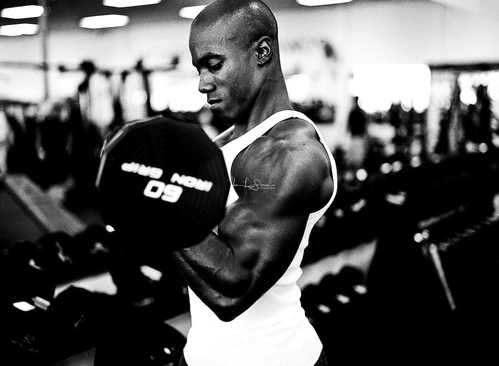 Anu McKnight, amateur bodybuilder, doing standing bicep curls with an EZ bar.