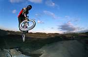 BMXer gets air off dirt mound, U.K, 2000s.