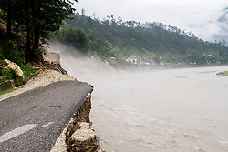 3rd July 2013. On the 16th and 17th June, the South West monsoon came earlier than expected with particularly heavy rain fall in the North Indian Himalayan state of Uttarakhand, the level of destruction is only just being realised as previously inaccessible areas are just being reached. Here a road has collapsed; as a result, locals have to carry supplies over and around mountains. MANDATORY CREDIT: © Sam Spickett/RedR India, under license to London News Pictures.